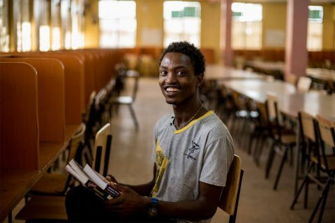 A scholar smiling and holding his textbooks in a classroom in Ethiopia